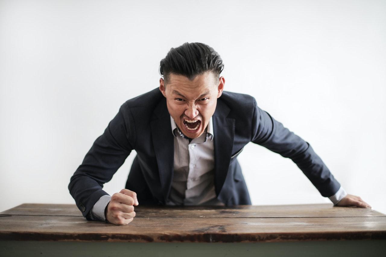 man yelling banging table
